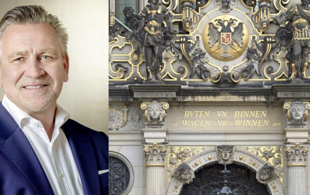 Olaf Mosel neben einem Bild der Handelskammer Bremen
